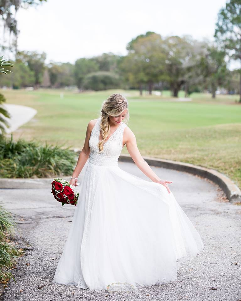 bride posing and holding dress skirt