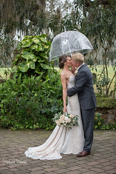bride and groom kiss under clear bubble umbrella