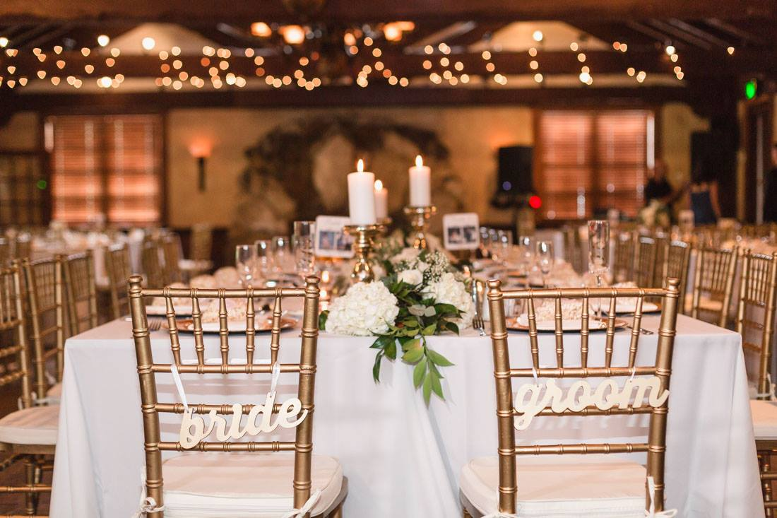 wedding reception dining tables with gold chairs