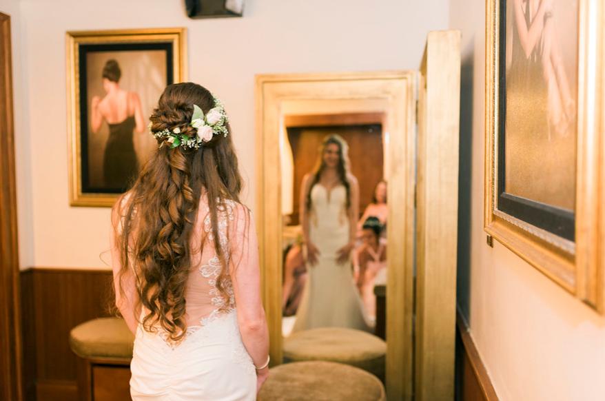 Bride standing at mirror in bridal suite