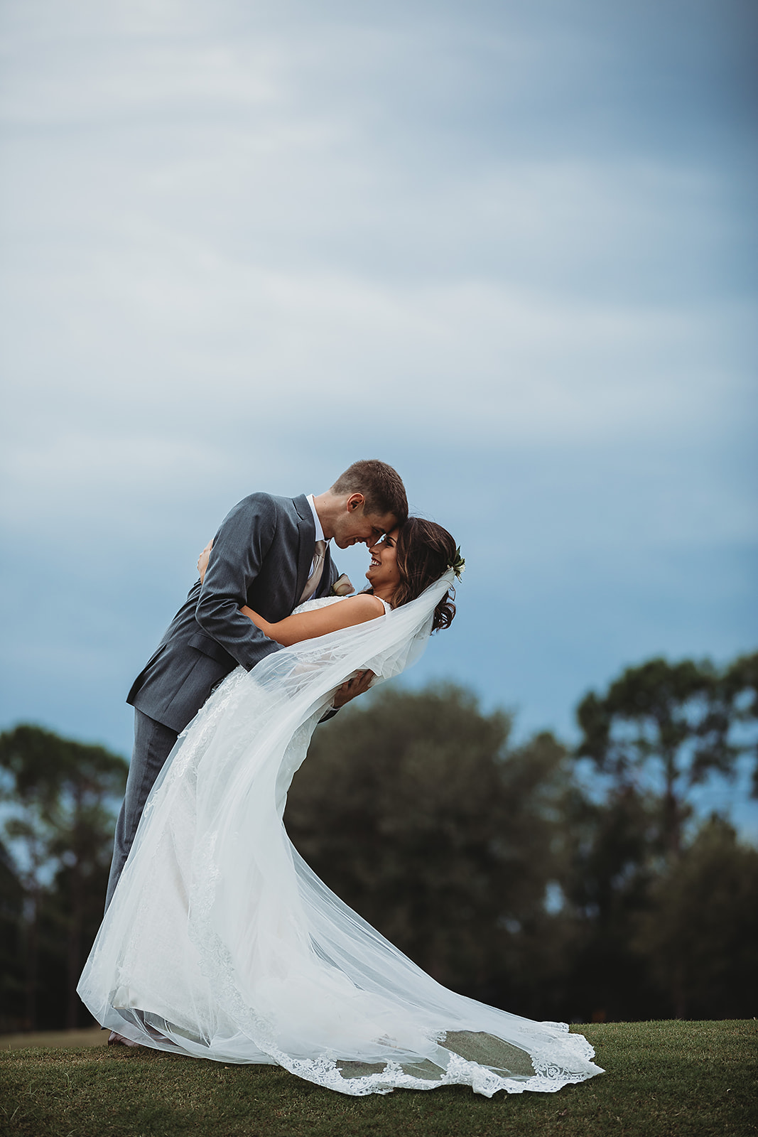 bride and groom kiss under a blue sky