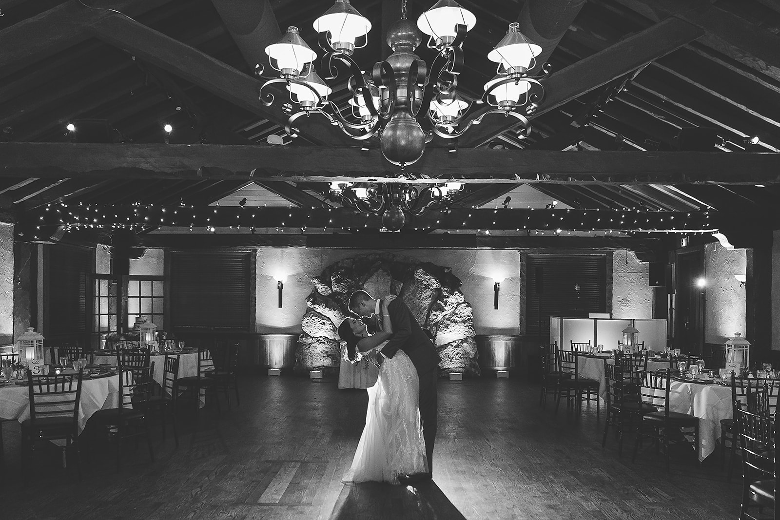 black and white photo of bride and groom dancing in ballroom
