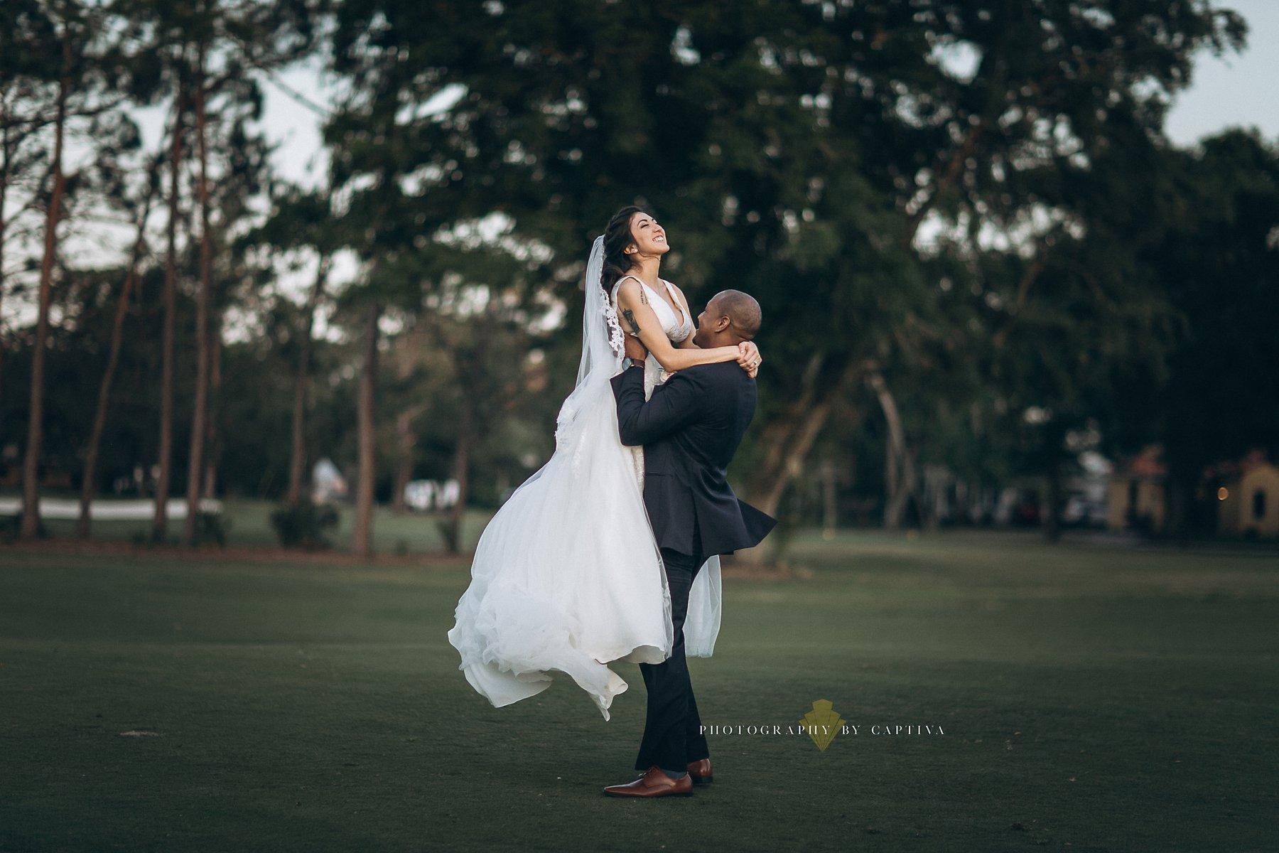 groom lifting bride up outside