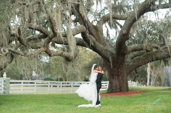 groom lifts bride as they kiss under tree