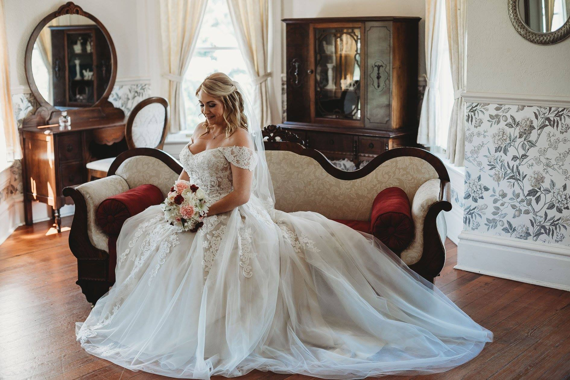 bride posing on settee in bridal suite