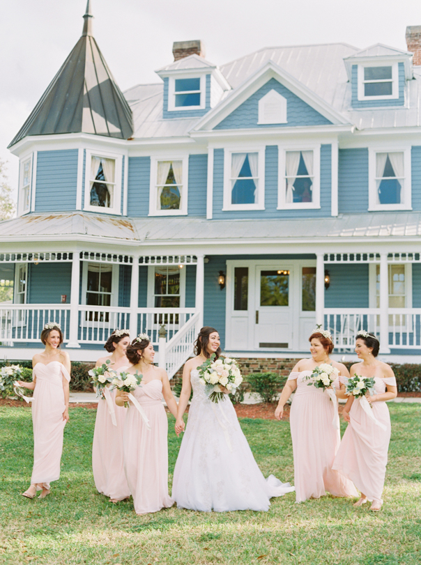 bride and bridesmaids posing in front of the highland manor
