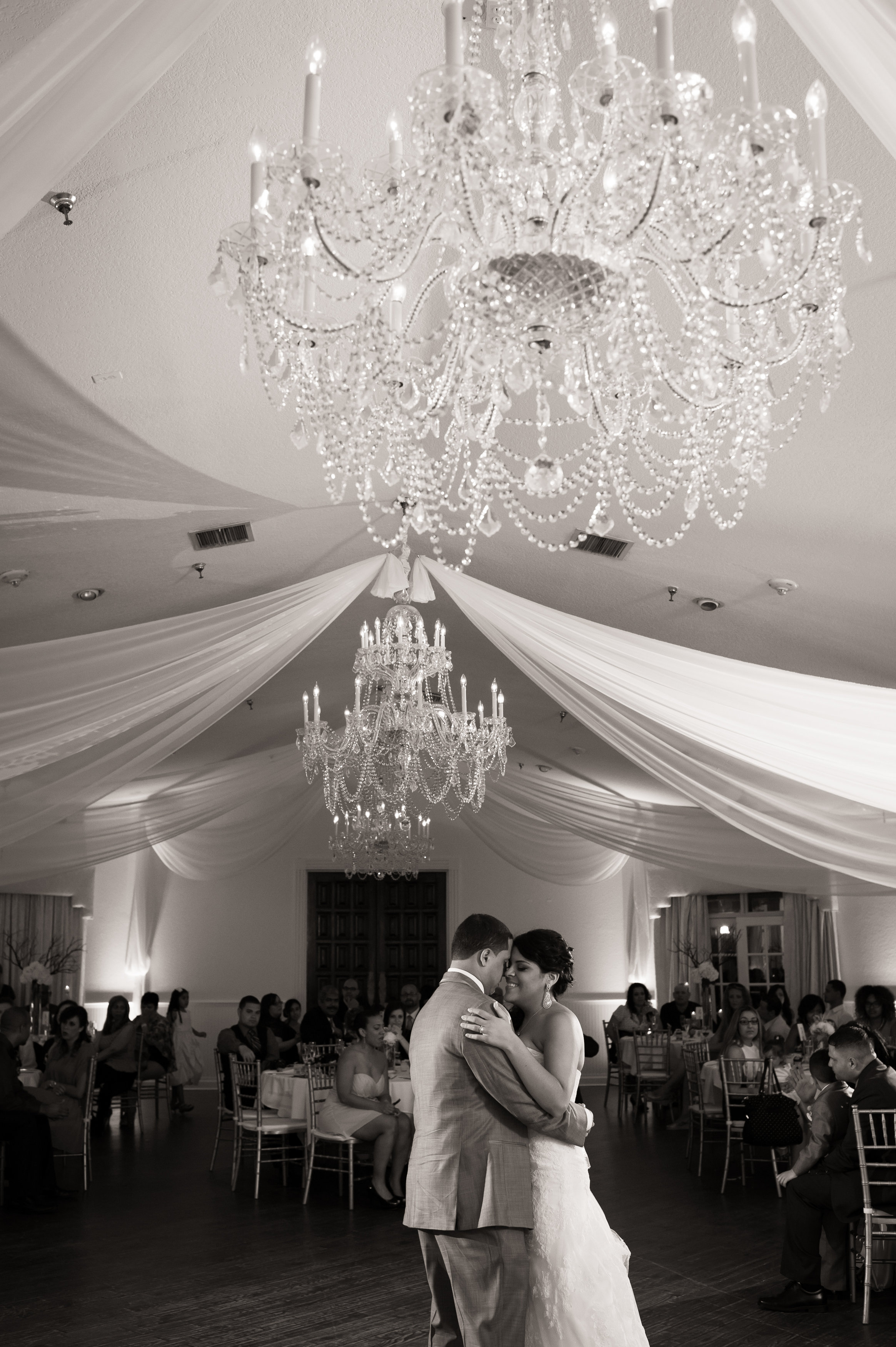 bride and groom posing beneath chandelier