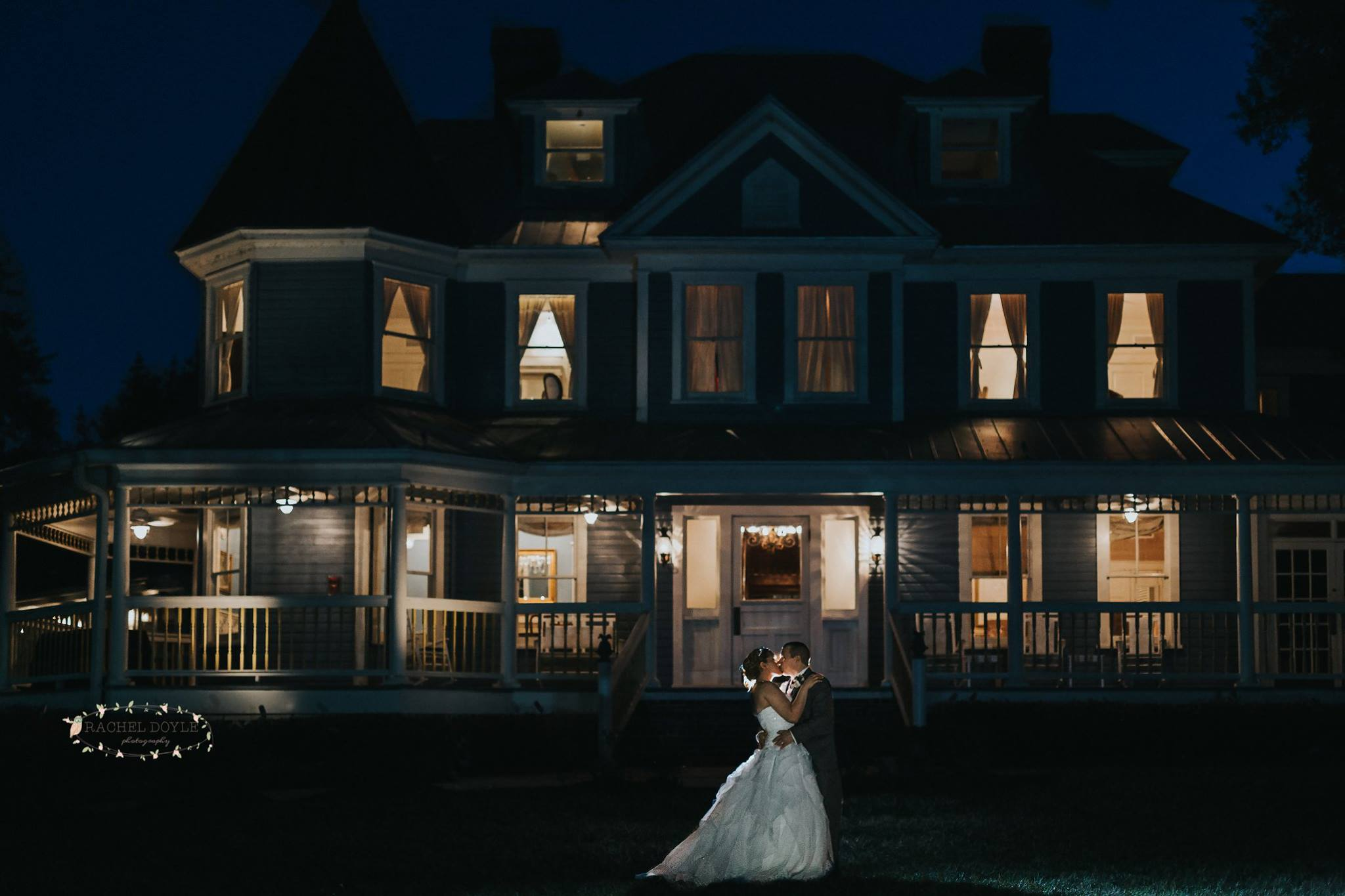 bride and bridesmaid posing in front of highland manor at night