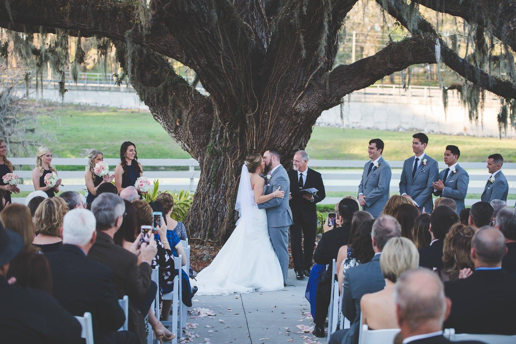 Bride and groom kiss under tree at ceremony