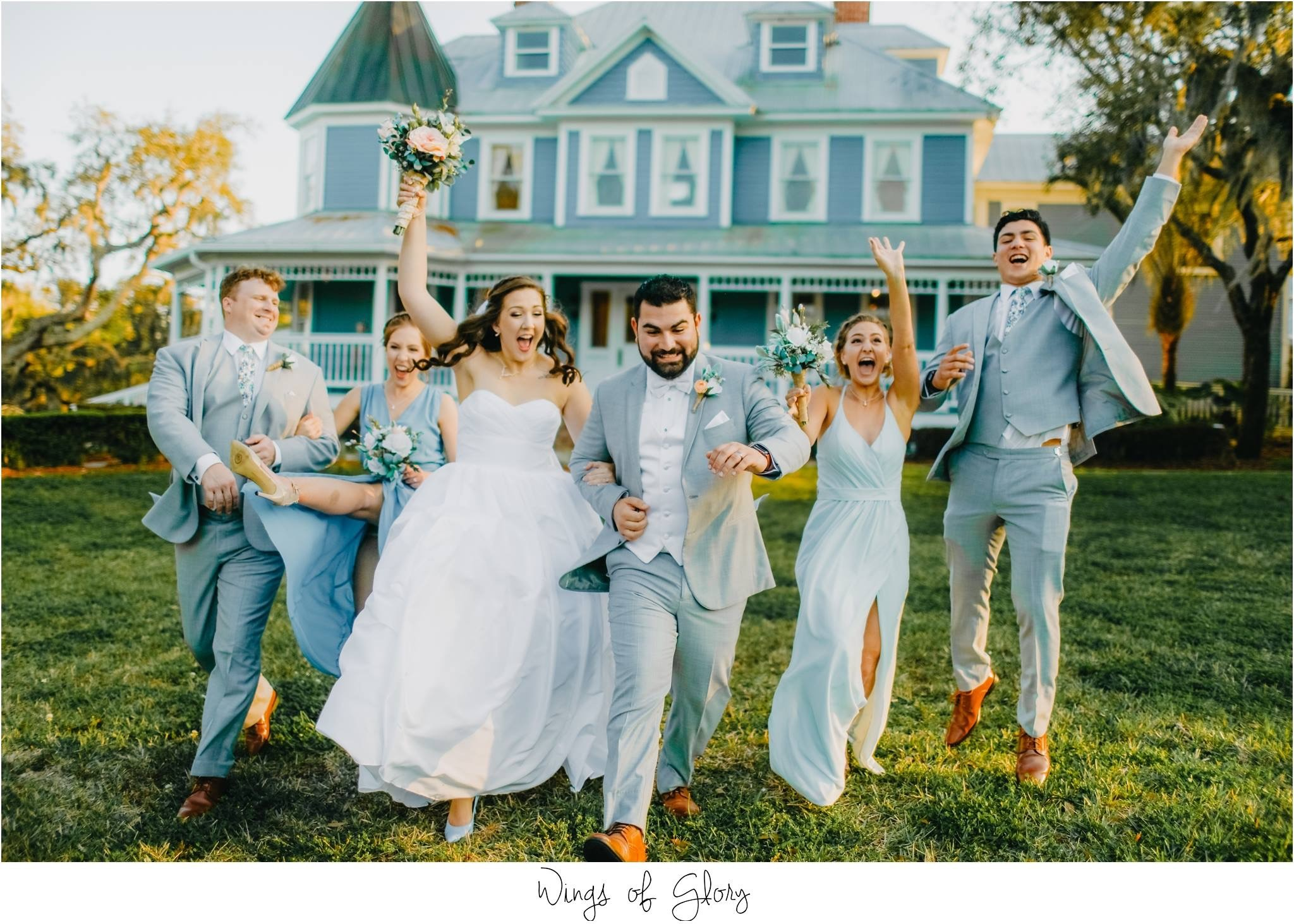 bride, groom, and wedding party posing in front of highland manor