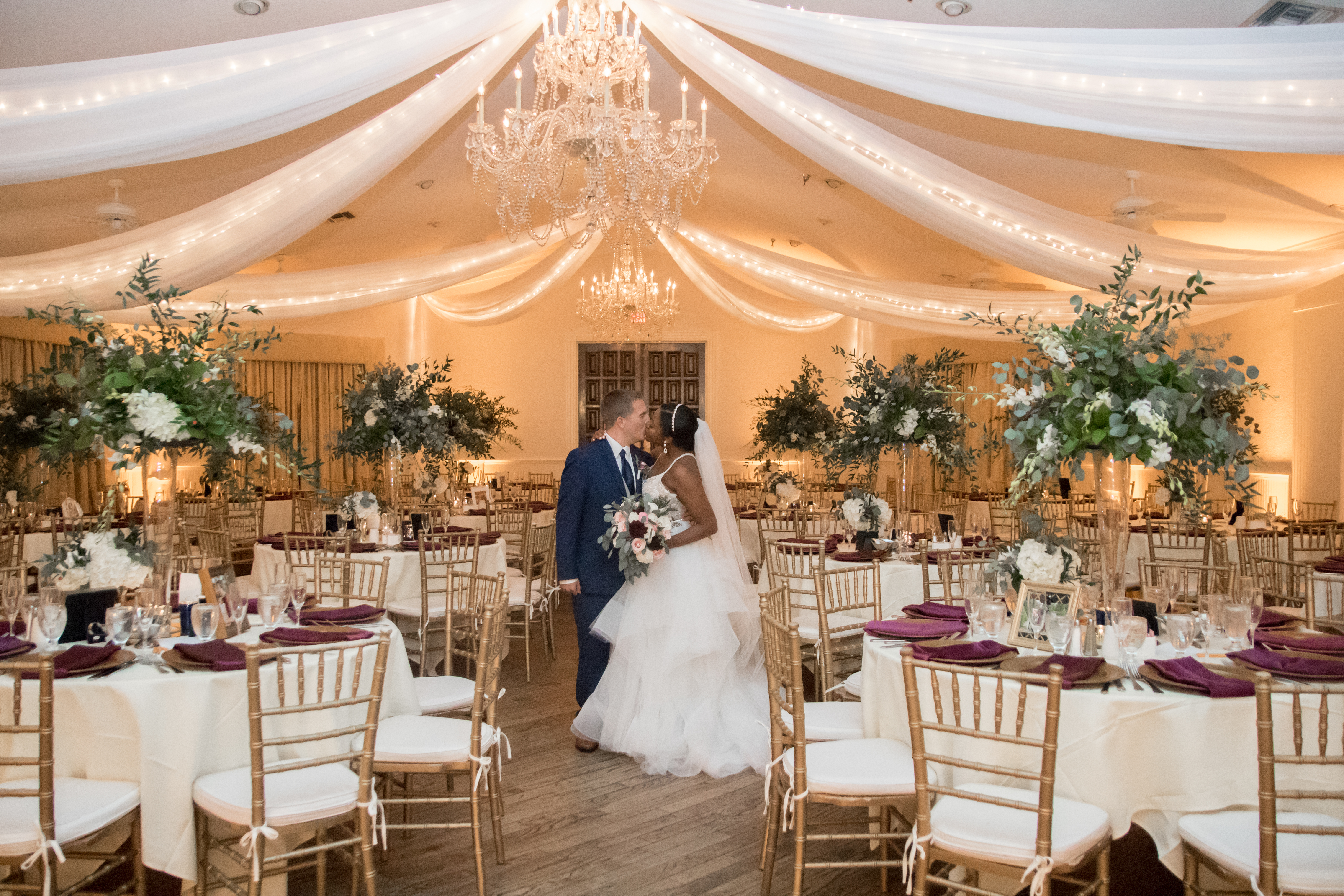 bride and groom kiss in the ballroom