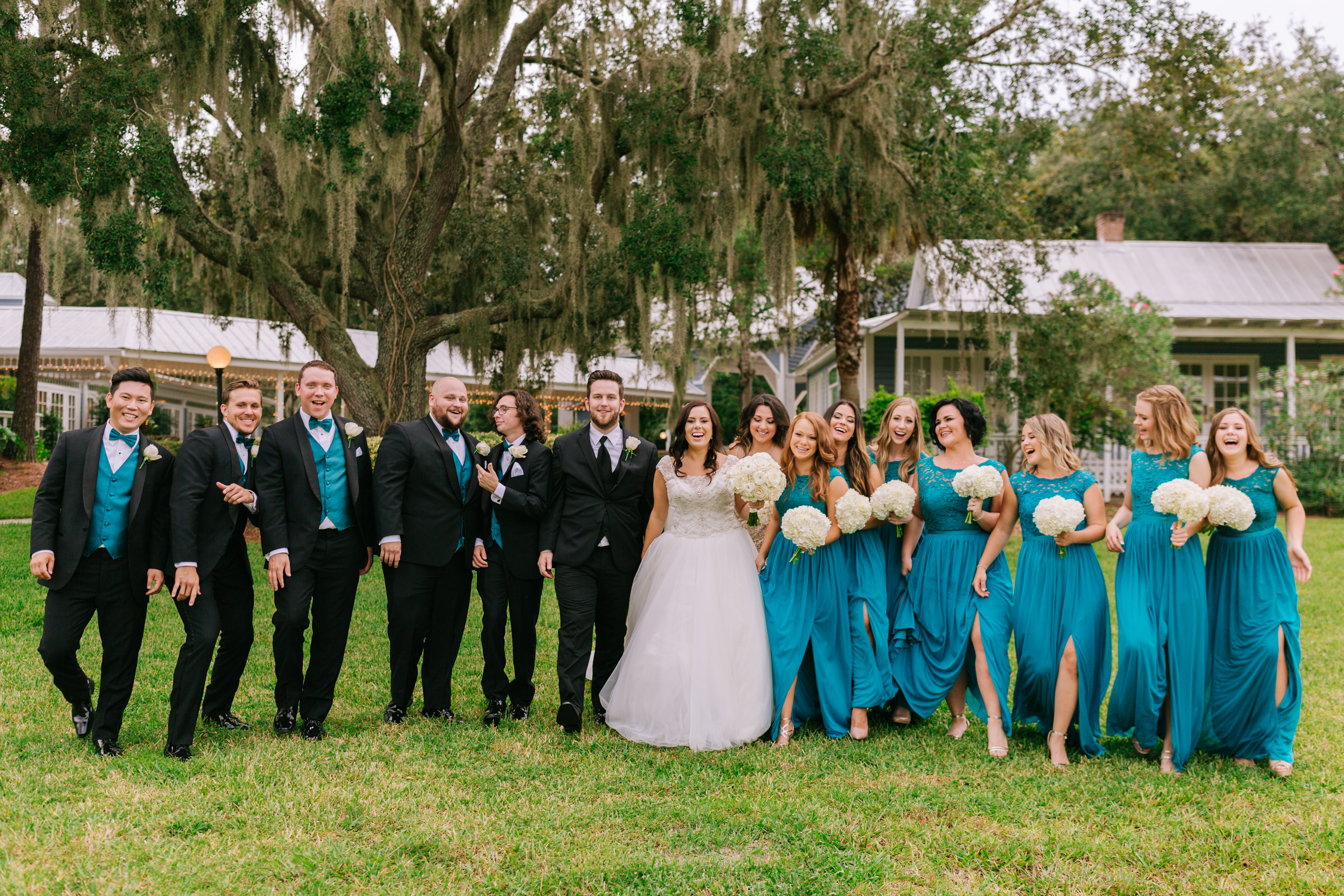 bride, groom, and wedding party posing in the grass