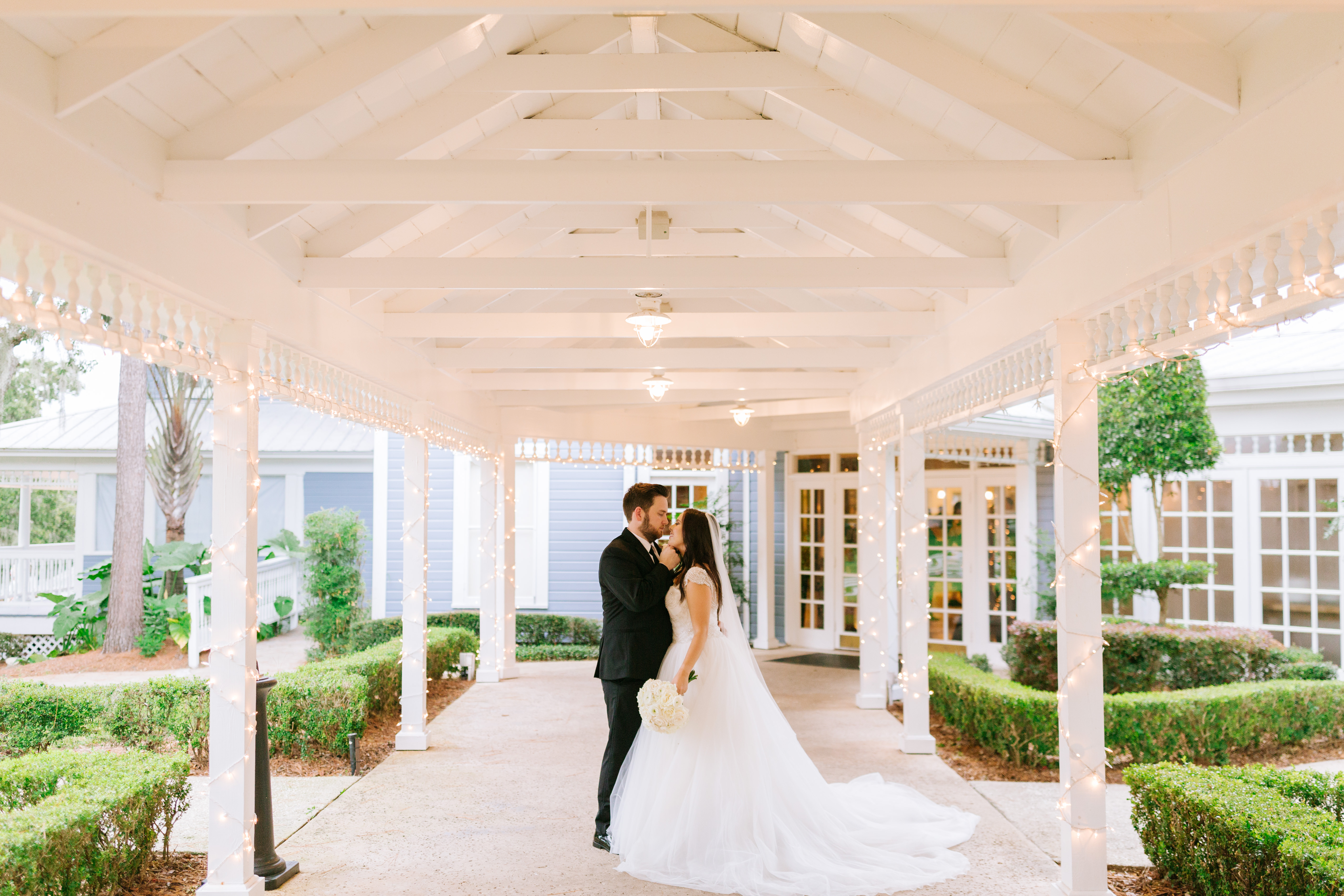 bride and groom kissing outside beneath awning