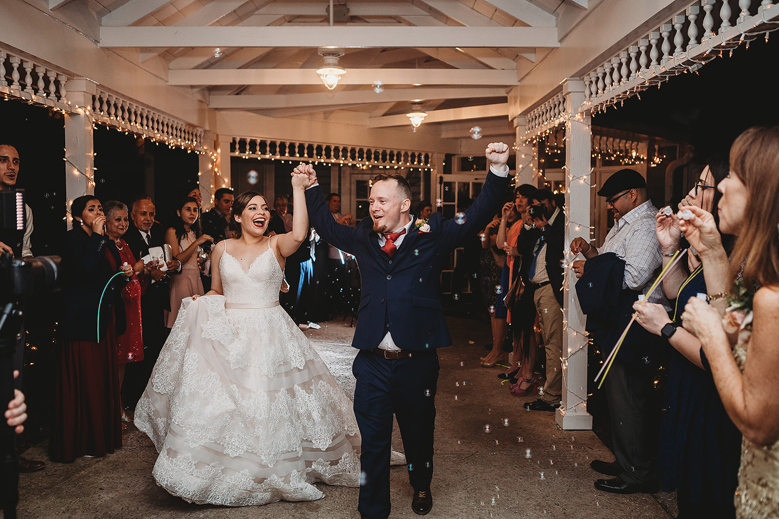 bride and groom walking through bubbles