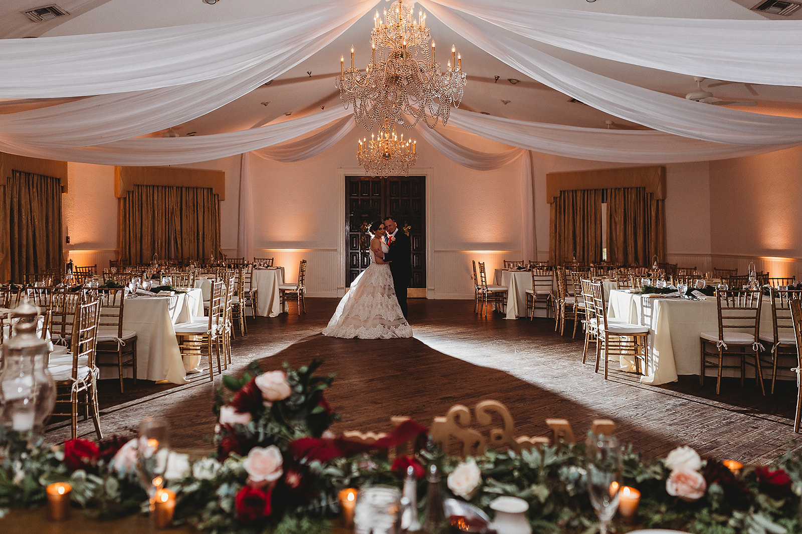 wide shot of bride and groom holding each other in the ballroom
