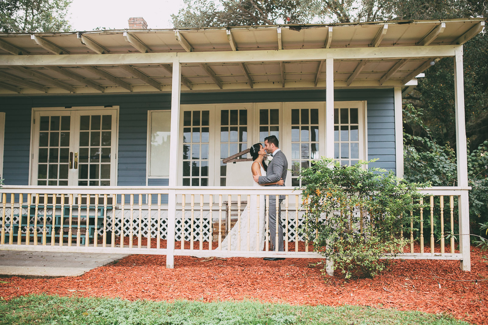 bride and groom posing on porch