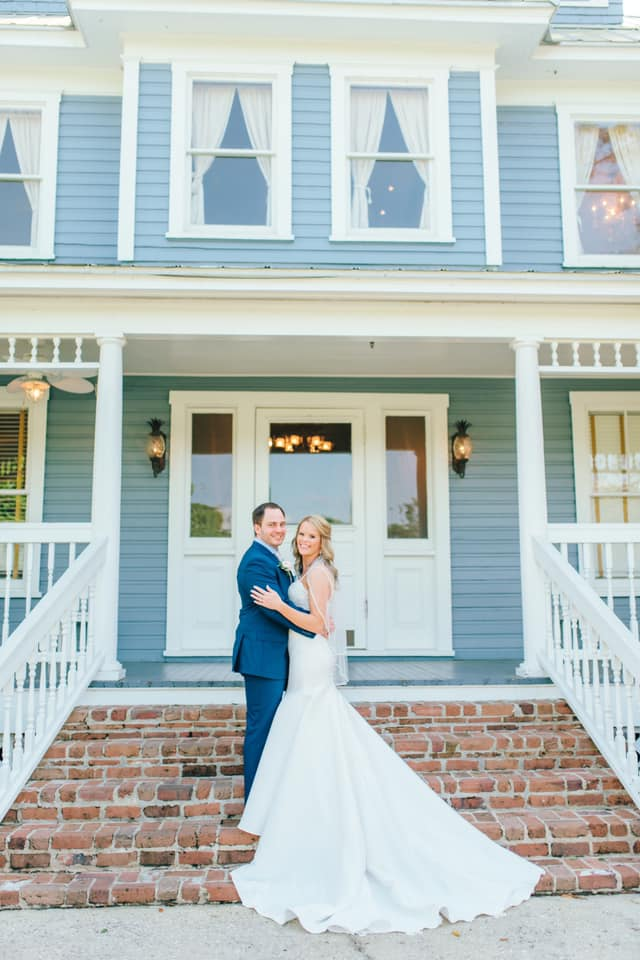 bride and groom posing in front of highland manor
