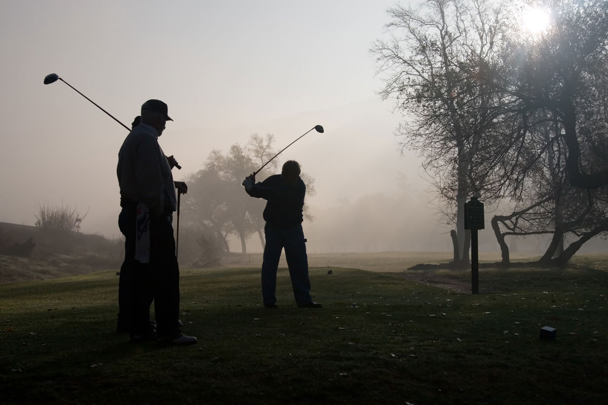 Golfers playing on a foggy Golf Course