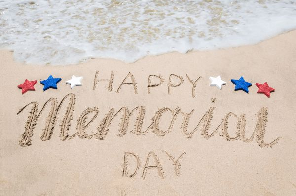 Happy Memorial Day written in the sand at the beach with water coming ashore