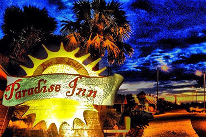 Paradise Inn sign brightly lit at night