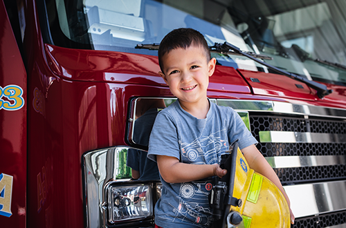 Child standing in front of a fire engine