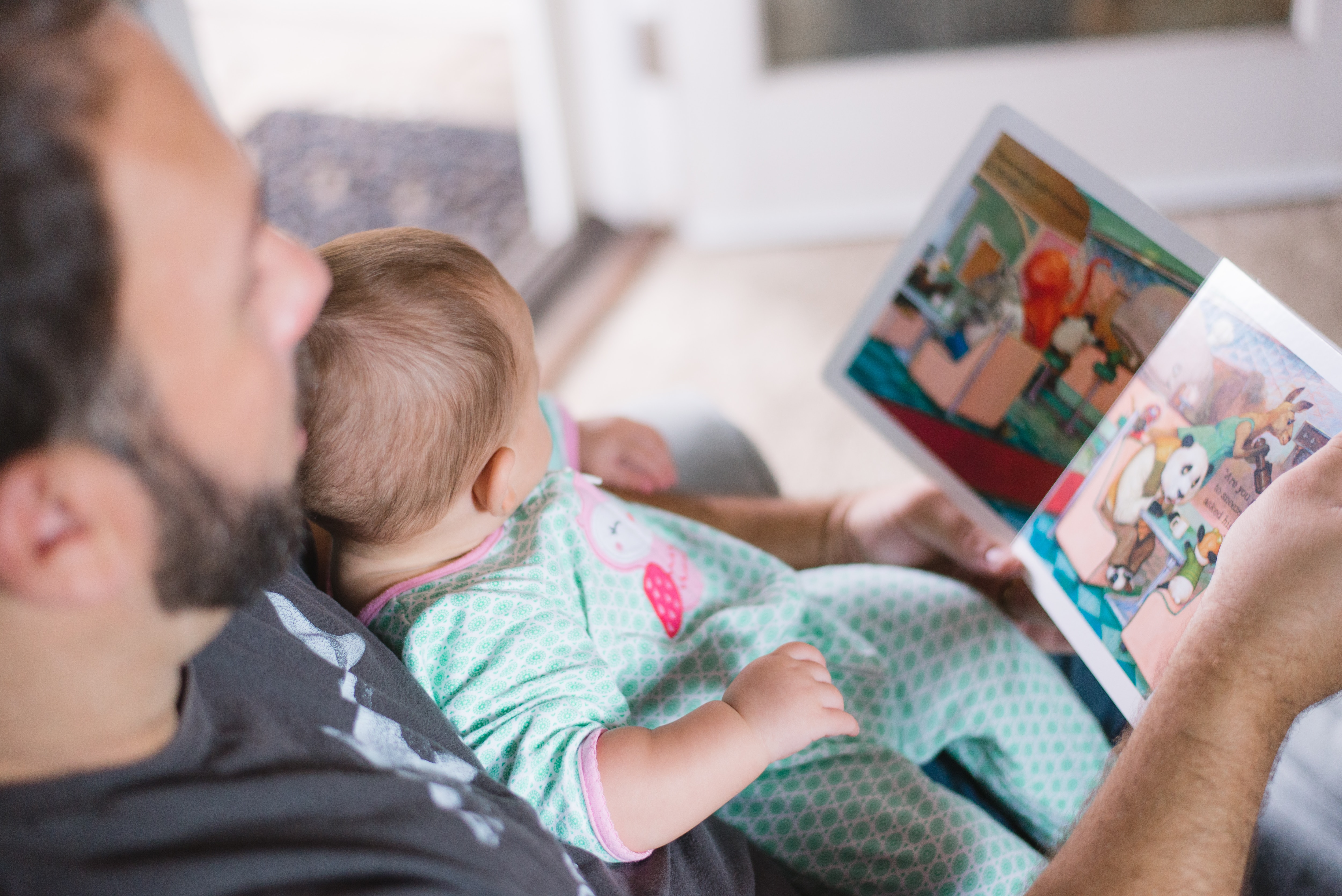 A father reading to his baby is another step in  building the baby's brain and preparing him for kindergarten