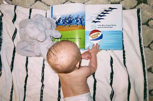 infant looking at picture book