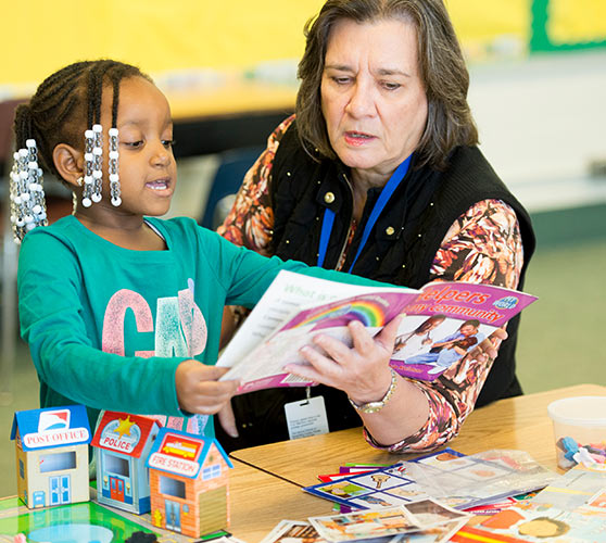 Woman helping a child read a book