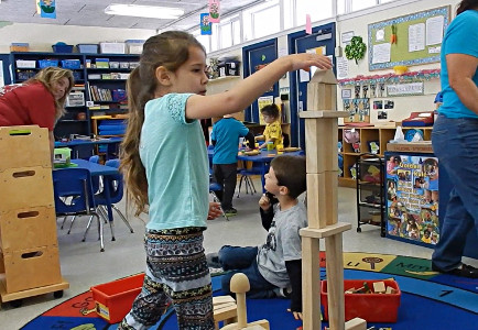 Little girl in a classroom building a structure with wooden blocks