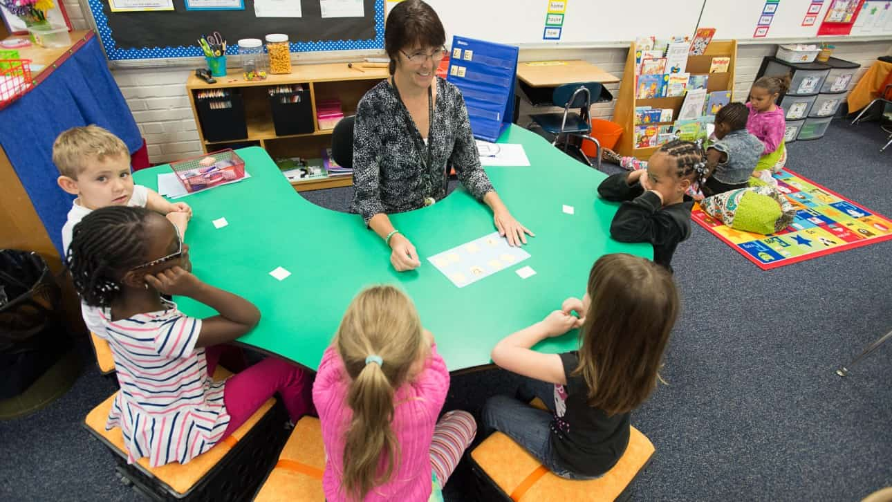 Teacher sitting at desk teaching 5 young students