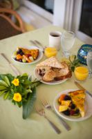 breakfast food on a table with vase of yellow flowers