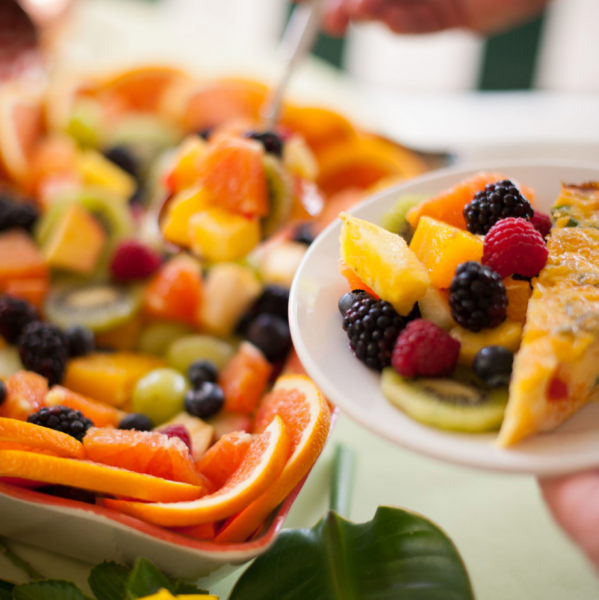 plate of fruit and quiche over a platter of fruit