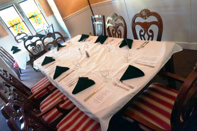 Large dining room table with chairs, white linens and silverware