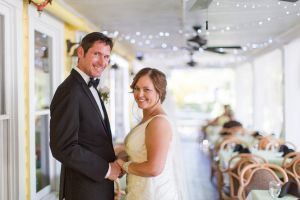 Bride and groom posing for a picture on a porch
