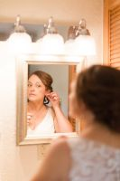Bride putting on her earrings in the mirror