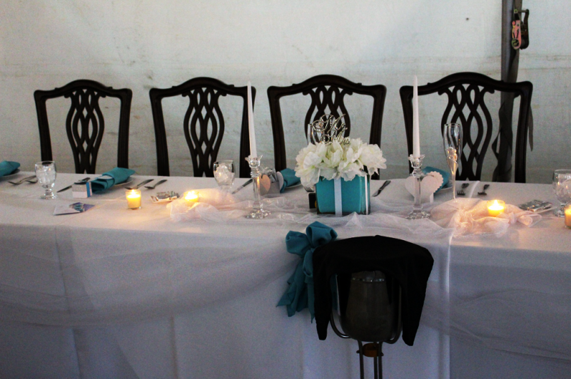 Long table for a bridal party with chairs  and white table clotbs