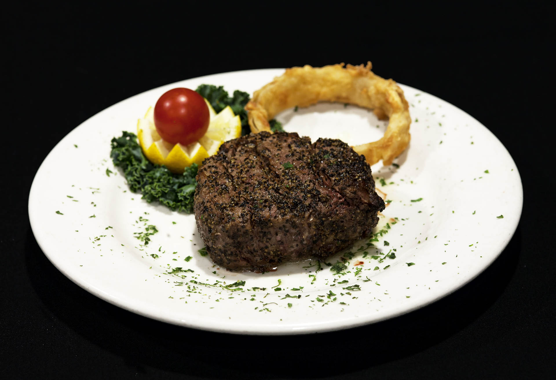 steak with onion ring, lemon, and tomato