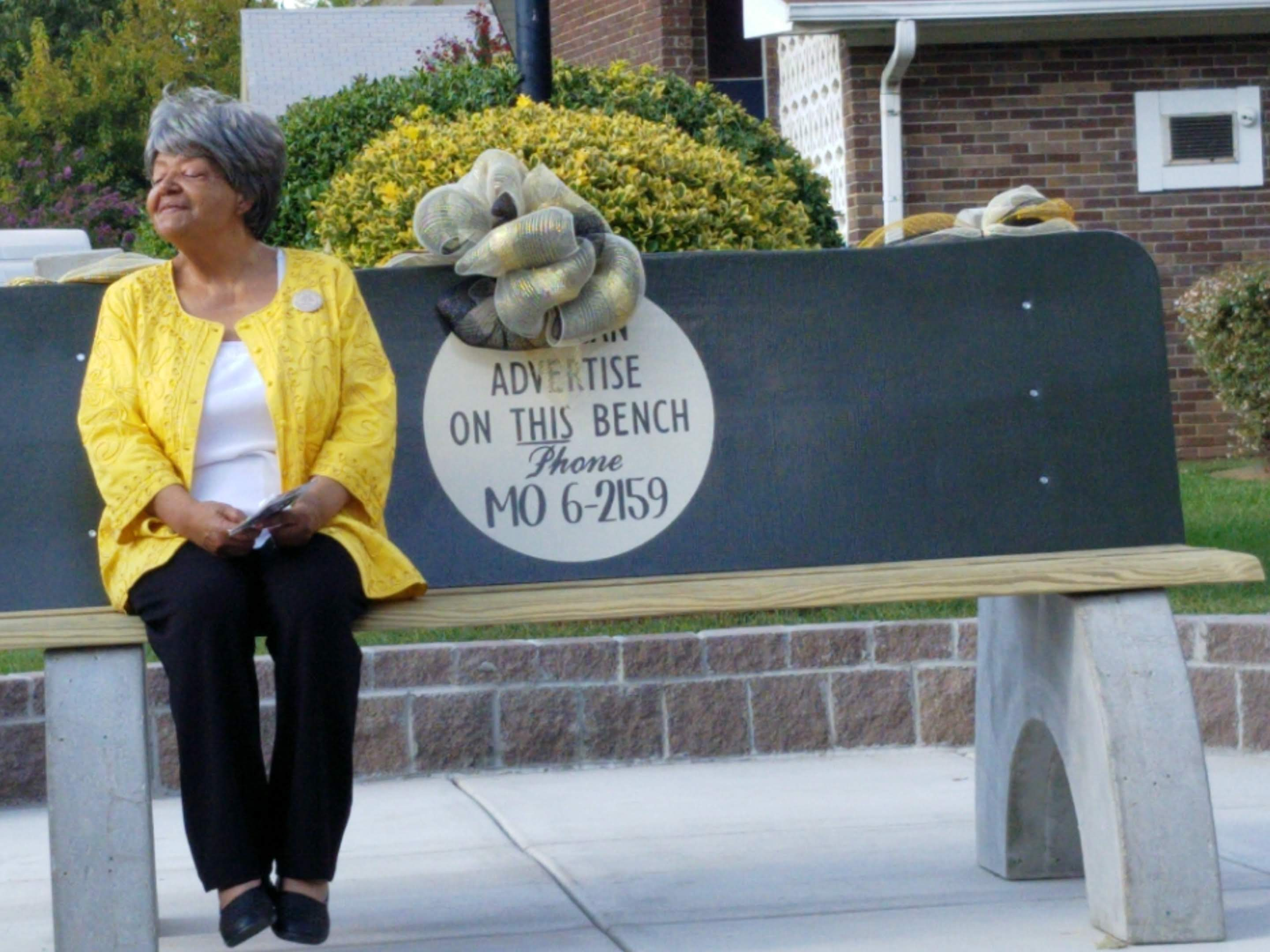 Elizabeth Eckford sitting on commemorative bench