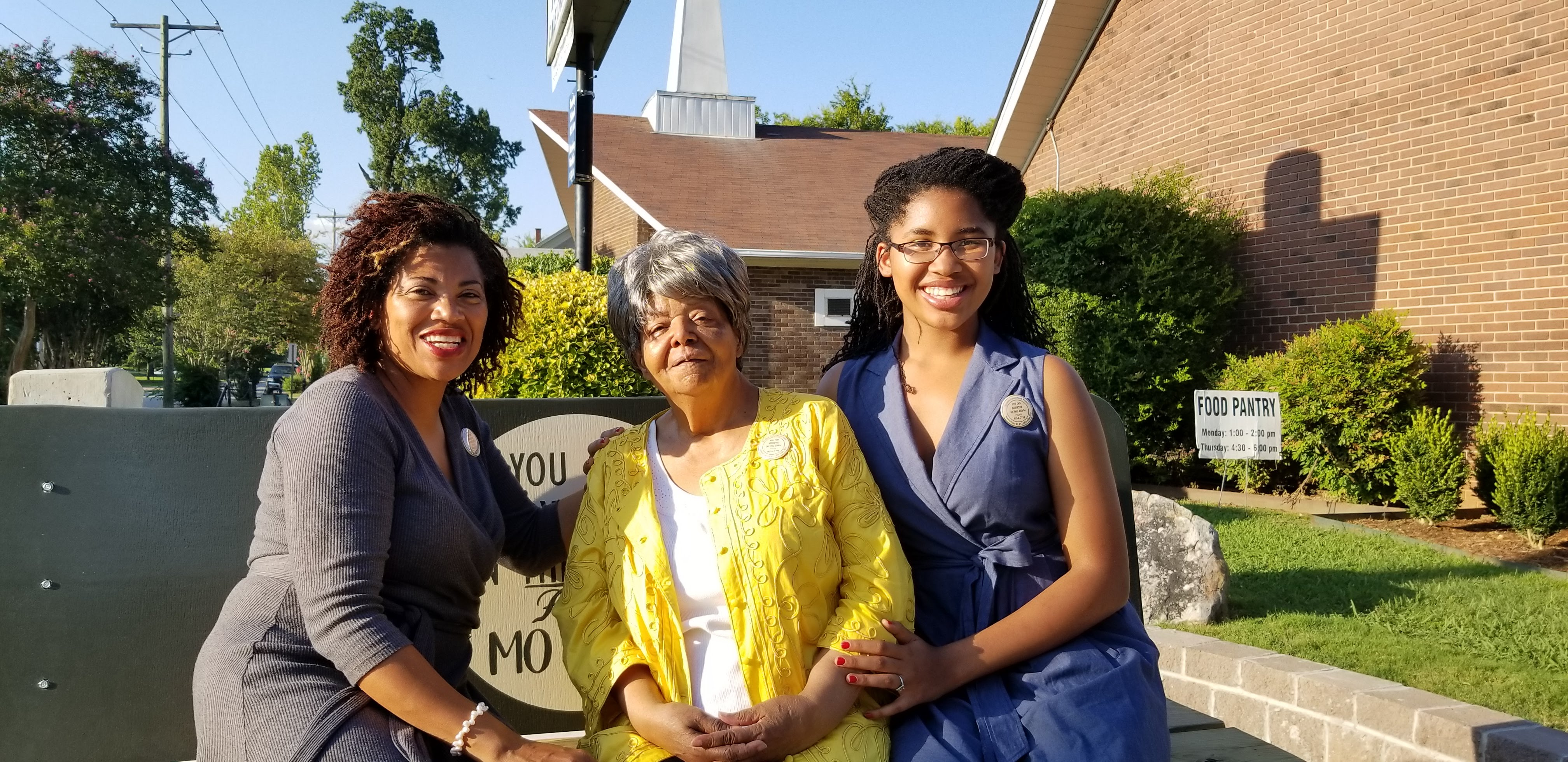Elizabeth Eckford, Eurydice Stanley, and Grace Stanley sitting on commemorative bench