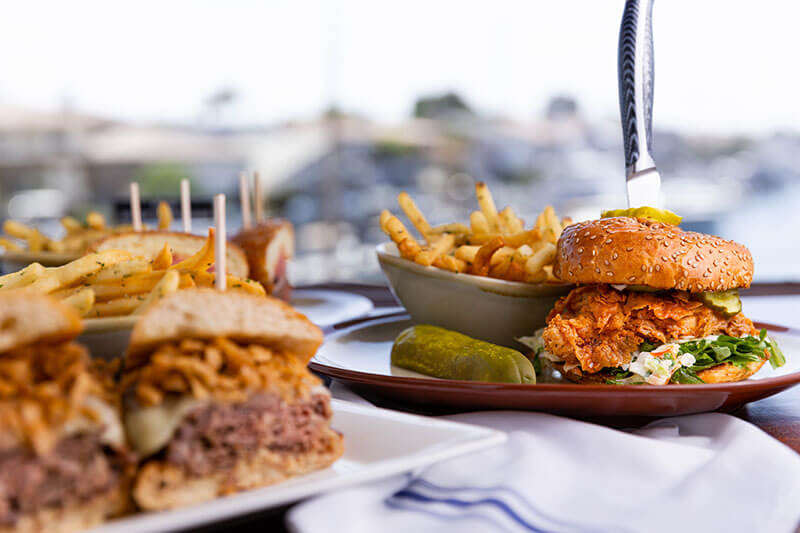 foreground: Prime Rib Dip - Gruyere Cheese, Crispy Onions, Creamed Horseradish, au jus / background: Fried Chicken Sandwich: Coleslaw, Bread & Butter Pickles