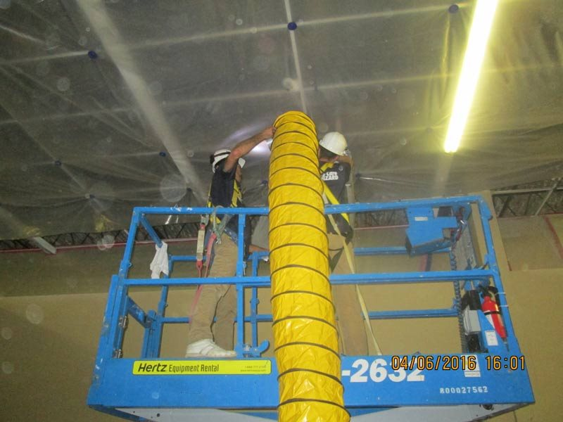 two employees on scissor lift holding a duct