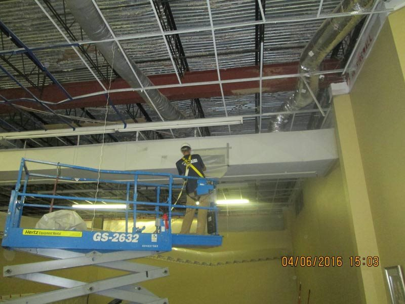 ACW technician on lift working on a duct