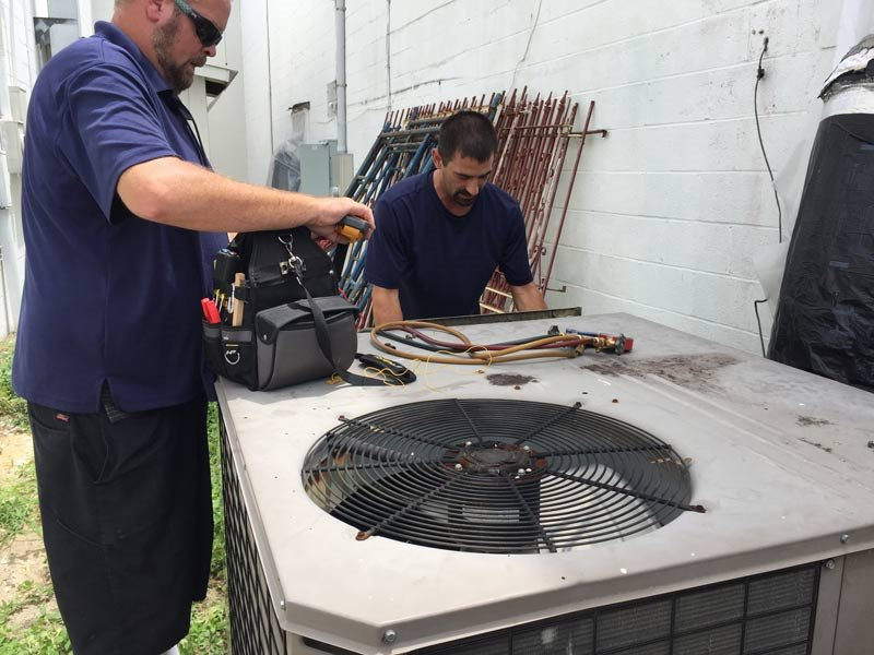 Two employees working on HVAC