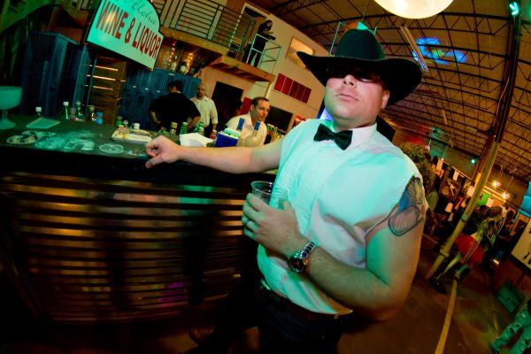 Dude wearing cowboy hat and bowtie standing next to the bar he built for Art Party 9