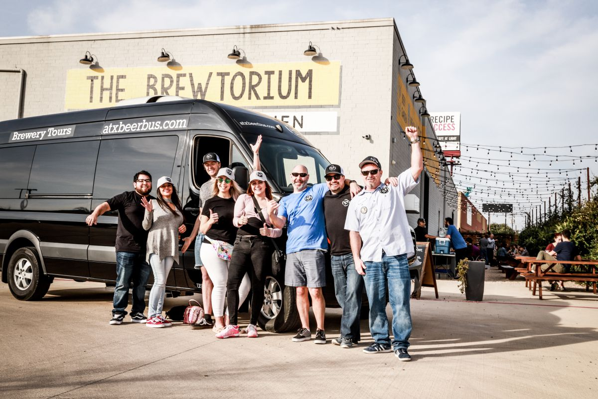 ATX Beer Bus riders cheering in front of vehicle and brewery