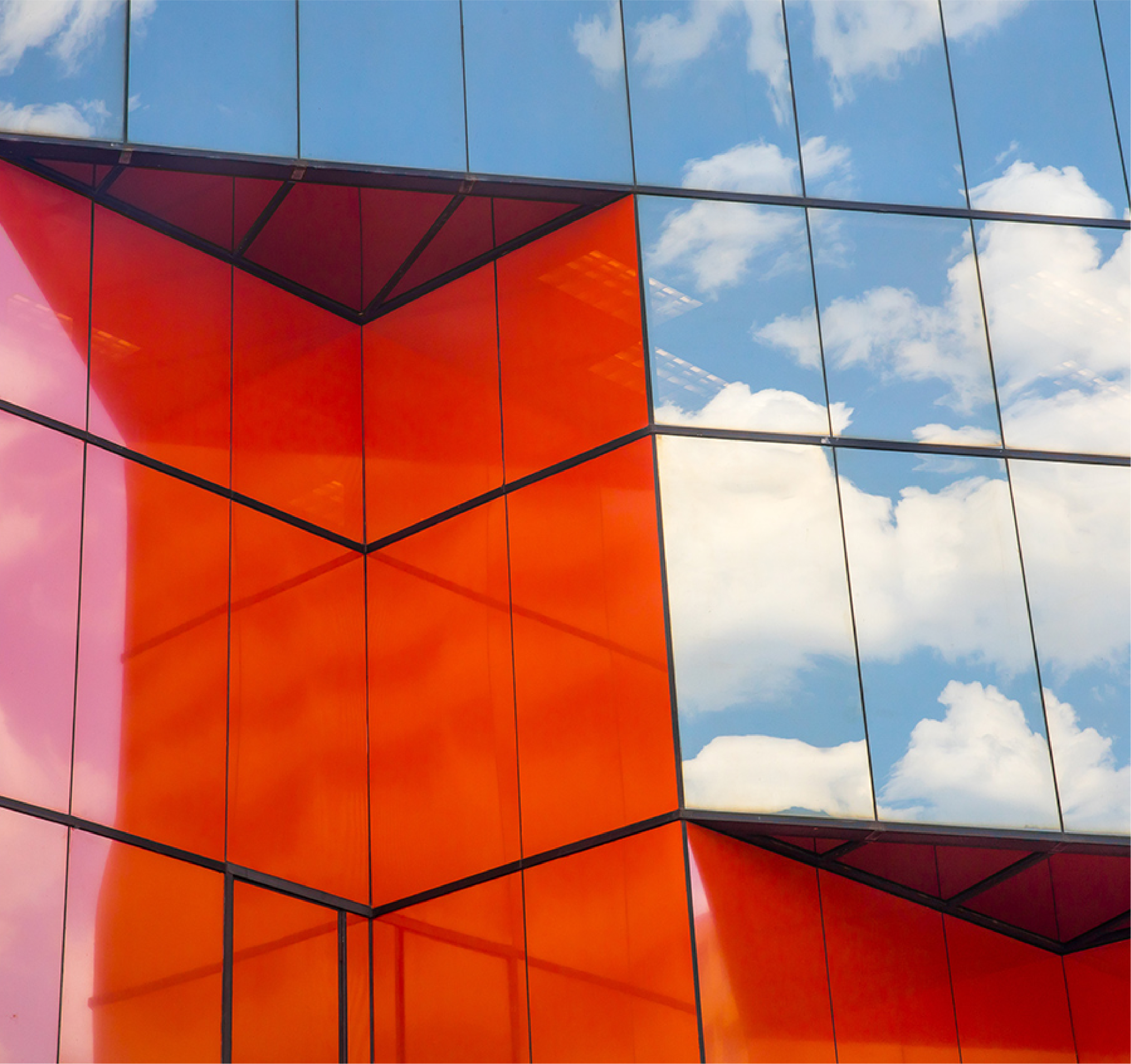 Building with glass construction reflecting clouds