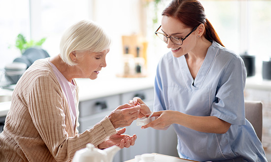 nurse giving medicine to older female