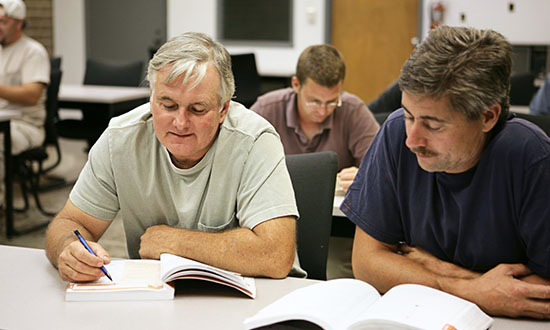two men looking at book in a classroom