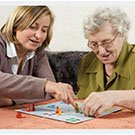 Caregiver playing a board game with a client