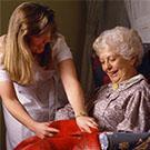 Caregiver putting a blanket on cient's lap